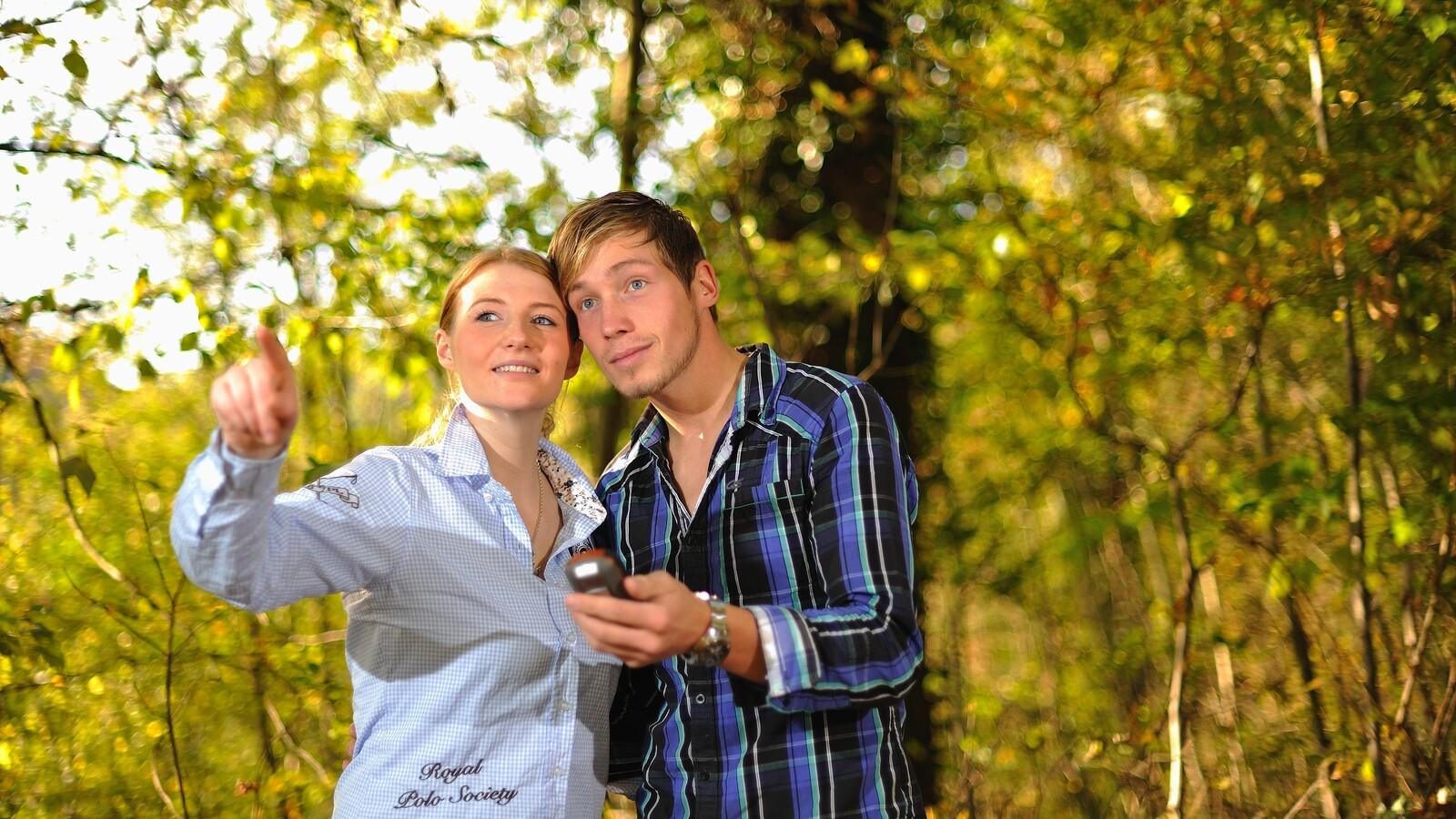 Mann und Frau mit GPS-Gerät halten Ausschau nach einen Cache